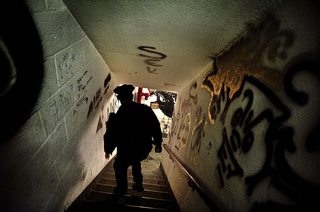Cop walking down a graffit-covered stairwell