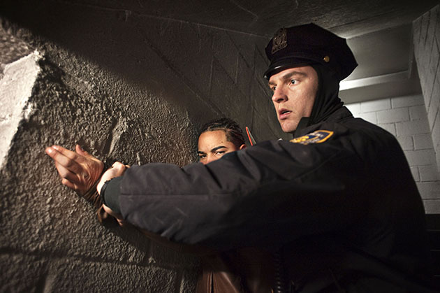 An officer detains a suspect inside a stairwell.
