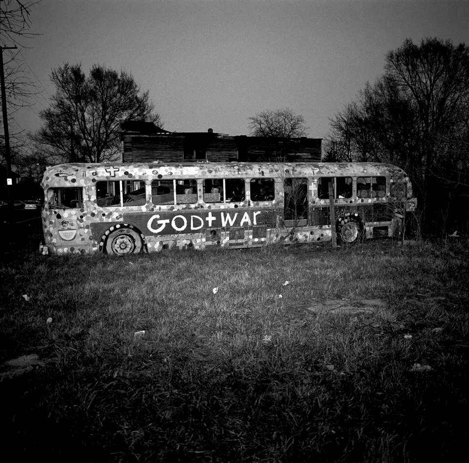 An abandoned bus in an empty lot.