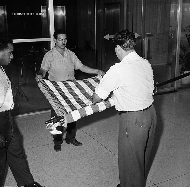 unidentified U.S. embassy employees rolling up a U.S. flag as the embassy transfers American affairs to the Swiss government, in Havana, Cuba.