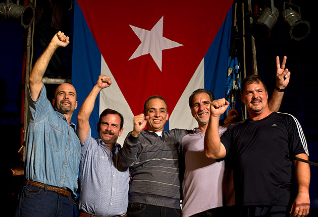 "Members of ""The Cuban Five,"" from left,  Gerardo Hernandez, Fernando Gonzalez, Antonio Guerrero, Rene Gonzalez and Ramon Labanino, wave to the public, in front of a Cuban flag after a concert of Silvio Rodriguez in Havana, Cuba, Saturday, Dec. 20, 2014. Guerrero, Labanino, and Hernandez flew back to their homeland on Wednesday in a quiet exchange of imprisoned spies, part of a historic agreement to restore relations between the two long-hostile countries."