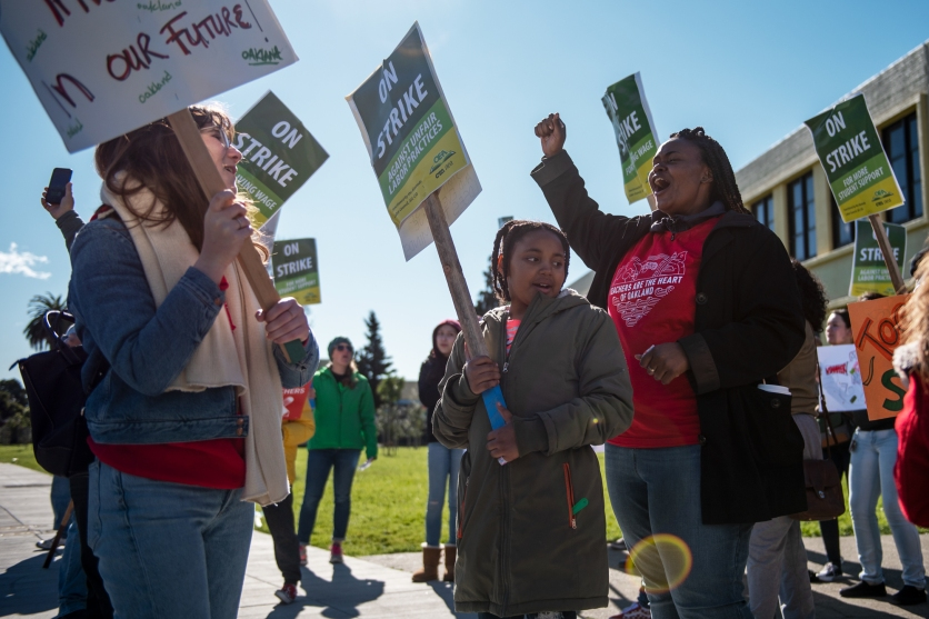 Magdaline Armstrong (right), a first-grade teacher, and her daughter Nilaya, eight, rally on a picket line with kindergarten teacher Grace Allen (left) outside Futures Elementary School.