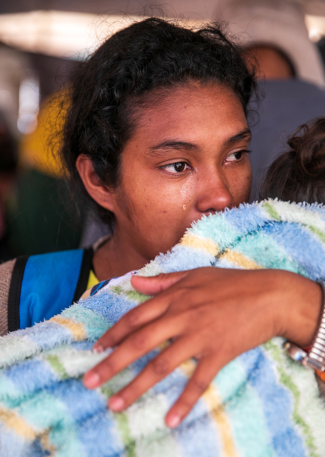 Arlen Cruz 22, wipes away a tear while holding her two year-old daughter in Tijuana, Mexico, on November 29, 2018.