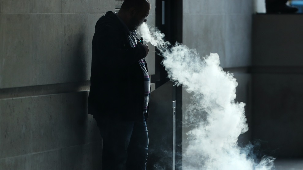 A bald man in shadow leans against a stone wall, exhaling a huge cloud of vapor.