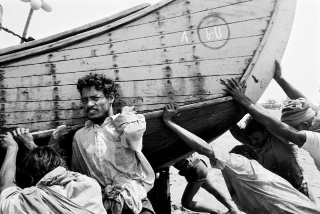 A group of Rohingya men push their fishing boat back onto shore. Most Rohingya men in the Shamlapur area of Bangladesh work as bonded laborers and are trapped into debt to local Bangladeshi boat owners.