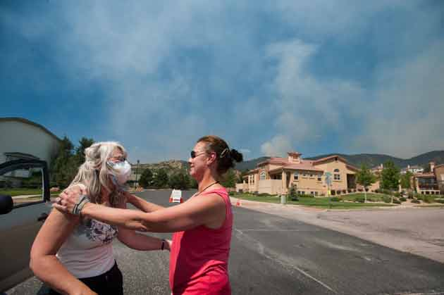 Two residents near the Waldo Canyon fire embrace as smoke rises over their neighborhood.  Mark Reis/Colorado Springs Gazette