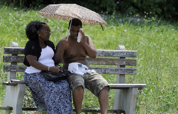 June 21, 2012 - A mother and her son try to beat the heat while waiting for a bus in Baltimore, Md.  Barbara Haddock Taylor/Baltimore Sun/ZUMAPress