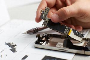 Wiens deconstructs a mobile device. Photo Chris Leschinsky