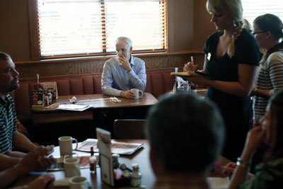 Bob Kerrey sits in a Scottsbluff diner, waiting to meet with ranchers and farmers.