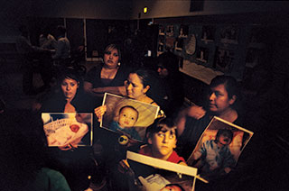 Kettleman City mothers—including Magdalena Romero, left, and Maura Alatorre, center—show photos of their babies to epa officials.